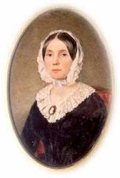 oval of young woman seated, with pinkish white frilled head bonnet and dress top, black narrow waist dress, straight dark hair parted in the middle