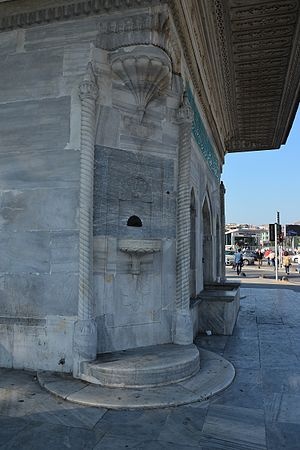 Fountain of Ahmed III (Üsküdar) - Details of a corner facade: A faucet over a sink flanked by two Solomonic columns topped with Corinthian order capital under a muqarnas. Cornice and eaves with ornaments carved at top.