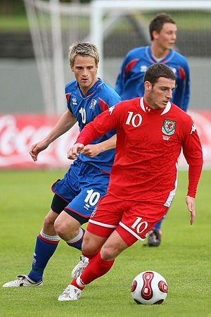 Jason Koumas - Koumas (red) and Gunnar Heiðar Þorvaldsson (blue) during international match between Iceland and Wales