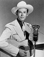 A young man wearing a cowboy hat, a jacket and tie, playing a guitar at a microphone