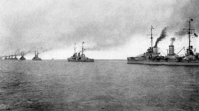 A line of nine large gray battleships stretches into the distance, all belching dark black smoke from their funnels