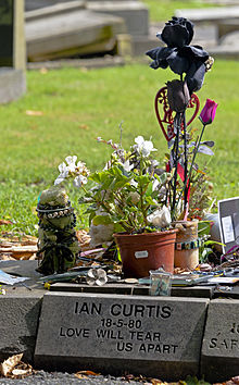 "A grayish stone block with ""Ian Curtis 18-5-80 Love Will Tear Us Apart"" carved into it in a sans-serif typeface. There are several small pots of flowers and other objects on top."
