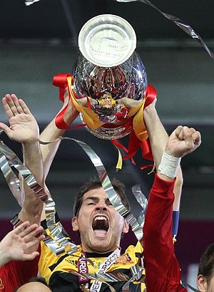 Iker Casillas - Casillas lifting the Euro 2012 trophy, the third consecutive major title for Spain, achieving a historic treble