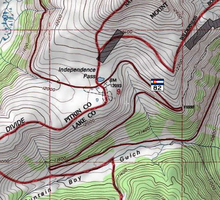 A topographic map of the pass showing Highway 82, the Continental Divide and the national forest boundaries in red on a white background with green areas