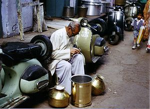 Craft - Street handicraft: here a skilled metalsmith in Agra, India sits between scooters in a commercial area making careful observations in the practice of his trade