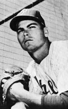 "A black-and-white photograph of a man wearing a white baseball uniform, pinstriped, with ""Phillies"" across the chest in script, and a dark-colored baseball cap with a white ""P"" on the front"