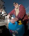 Jeff Heath, of CMS Oilfield Services, fills a container with water for a resident affected by the Elk River water contamination at Poca High School in Poca, W.Va., on Jan. 11, 2014 140111-Z-LQ742-013.jpg
