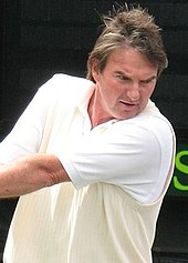 A man wearing white clothes swinging a tennis racket