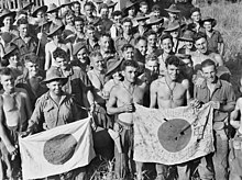 A crowd of men, some shirtless, some wearing slouch hats, hold up two rising sun flags. One has Japanese writing on it.