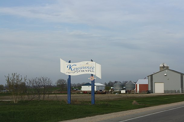 Welcome sign on WIS 54, farm in the background