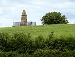 Stone obelisk surrounded by railings set in green fields and trees