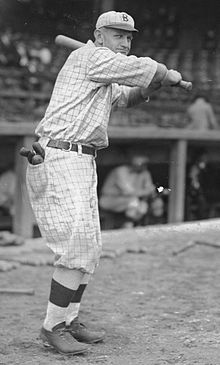 A man wearing an old-style checked baseball uniform holds a baseball bat over his left shoulder.