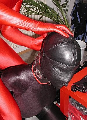 "Bondage hood - A submissive wearing a zentai and a full-faced leather bondage hood or ""gimp mask"" that features a ring attachment at the nose and barely visible nostril openings."