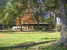 Leaves are turning red on trees in a park graced with a covered picnic shelter on a wide green lawn. Homes are visible on the far side of the park.