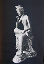 Three-quarter view of a seated statue in half-lotus position. The right foot rests on the left upper leg, the right elbow rests on the right knee with the right hand close to the head in contemplating pose.