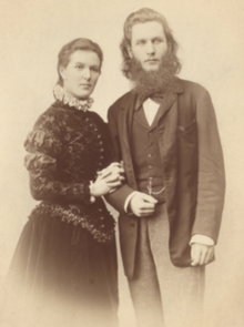 Portrait of a standing woman in Edwardian dress holding the arm of a standing bearded man.