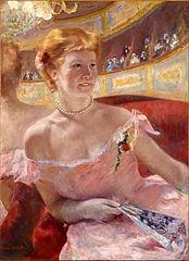 Femme avec un collier de perles dans une loge