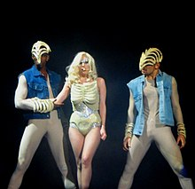 A blond woman in a nude colored leotard is flanked by two males in nude body suit and blue jacket. The woman's chest and the hand and head of the two males are covered by skeletal masks. The woman has glitter surrounding her eyes.