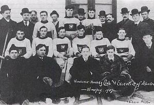 Several rows of men, some wearing hockey uniforms, the others in overcoats and top hats.