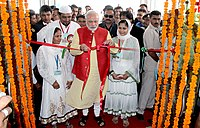 Modi unties a ceremonial red ribbon before a crowd of onlookers