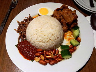 Nasi lemak - Nasi lemak is served with anchovies, peanuts, boiled egg, lamb curry, cucumber, and sambal.