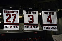 Three banners with the New Jersey Devils retired numbers, showing the player surname and years with the team: Niedermayer, 27, 1991–2004; Daneyko, 3, 1982–2003; and Stevens, 4, 1981–2005.