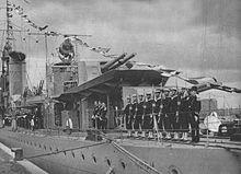 Widok rufowej części okrętu – od rufy do komina, który widać w głębi (ujęcie skrócone). Okręt stoi zacumowany do nabrzeża, z podniesioną pełną galą banderową, na rufie wzdłuż burty (na torach minowych od rufy do wysokości stanowiska nr 4 dział 120 mm) stoi w szeregu pododdział marynarzy w mundurach galowych, prezentując broń.
