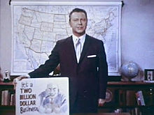 "A still shot from the 1965 film Perversion for Profit showing a man in a suit holding a placard. The placard features a cartoonish image of a leering man and the phrase ""It's a two billion dollar business"""