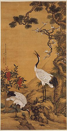 Two cranes near a pine tree. One is feeding on the ground while another rears its head high. Red flowers are also in the background