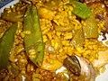 Plato de paella de arroz con tirabeques y caracoles.jpg