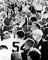 President John F. Kennedy performing the ceremonial coin toss at the Orange Bowl game Miami, Florida (8161029350).jpg