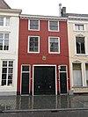 foto van Huis met geelgeverfde lijstgevel en kroonlijst op klossen