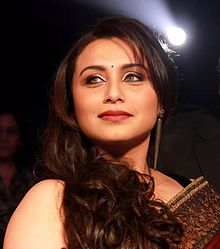 Rani Mukerji is dressed in a red saree and is smiling away from the camera