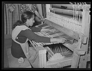 Rug making - Woman passing a shuttle through the warp on a loom.