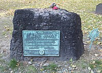 "A rectangular, rough-hewn block of stone on the ground. There is a walkway in the foreground, grass and trees in the background. A weathered plaque on the stone reads: ""Samuel Adams, Signer of the Declaration of Independence, Governor of this Commonwealth, A Leader of Men and an ardent Patriot."""