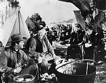 a gathering of men in an American West scene with the two in the foreground peeling potatoes
