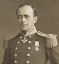 Man with receding hairline  , looking left, wearing naval uniform with medals, polished buttons and heavy shoulder decorations
