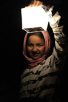 14 year old Syrian refugee girl at night dressed with a head scarf is illuminated by holding up a Solar lantern called SolarPuff in the Idomeni refugee camp in Greece 2015
