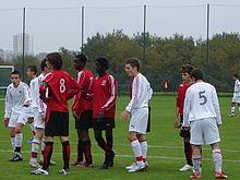 Photographie présentant un groupe de joueurs de 14 ans disputant un match de football.