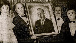 "Stanley Steingut - Stanley Steingut receiving portrait from Crown Heights Yeshiva for ""'distinguished constributions' in fostering educational growth of the community."" Madeline Steingut on left. Abe Beame on far right."