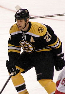 "A hockey player in a Black uniform with gold trim and a stylized ""B"" logo on his chest defends his position during a game."