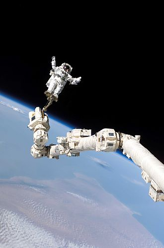 Extravehicular activity - Stephen Robinson riding the robotic arm during STS-114, doing a first in-flight repair of the Space Shuttle. The landmass in the backdrop is the Bari region of Somalia.