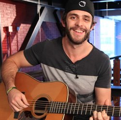 A bearded young man smiling broadly and playing a guitar