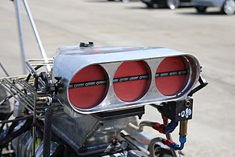 Throttle - Triple butterfly throttle body atop a fuel injection plenum, on a supercharged drag racing car