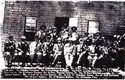 A black-and-white photograph of a group of men standing and sitting in front of a war damaged building. The caption at the bottom lists the names of those present