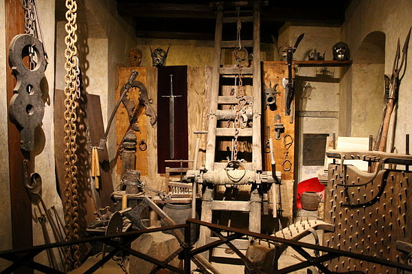 Torture tools in Prague Castle; note spiked ladder rack, shrew's fiddle, and, at center left rear, a spiked wooden screw press applicable to elbows, knees, or feet Torture chamber in Prague Castle.JPG