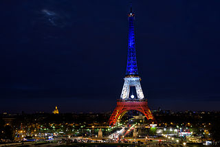 The Eiffel Tower illuminated in the colors of the French flag.