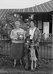 Two lady golfers outside Llandrindod Wells Golf Club pavilion, one holding the Open Challenge Bowl, 1933