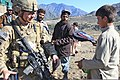 U.S. Army Cpl. Chris O'Brien, left, with the 312th Psychological Operations Company assigned to 2nd Battalion, 27th Infantry Division at Forward Operating Base Bostick, Afghanistan, hands a school backpack to an 111113-A-RR514-961.jpg