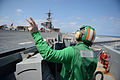 U.S. Navy Aviation Boatswain's Mate (Equipment) 2nd Class Zachary Everett signals to the aircraft launch and recovery officer April 24, 2013, on the flight deck of the aircraft carrier USS George H.W. Bush 130424-N-FU443-899.jpg